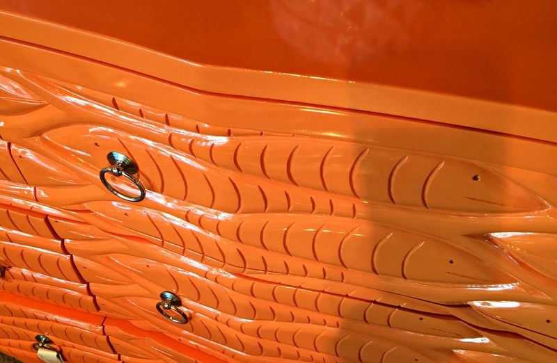 Close up of glossy orange chest with carved fish design