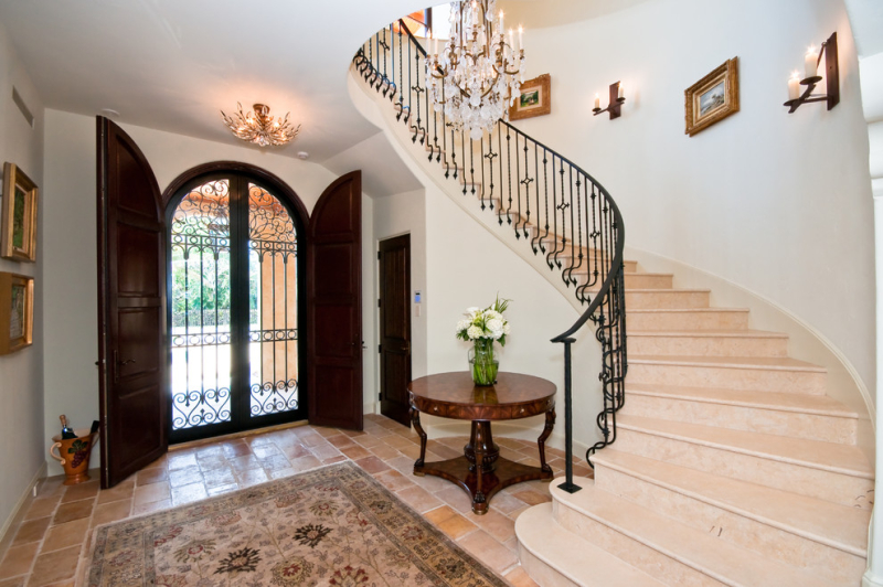 Impressive-wrought-iron-candle-sconces-with-wrought-iron-door-next-to-curved-staircase-and-arched-front-door