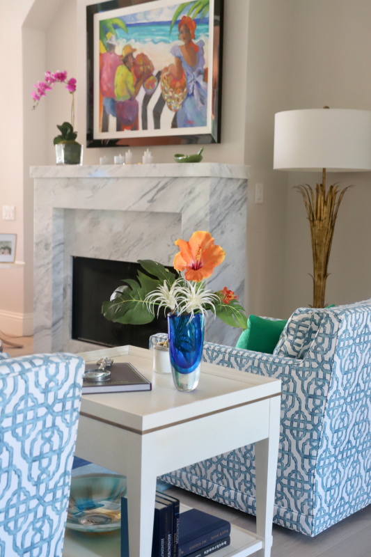Orchid on fireplace with blue chairs